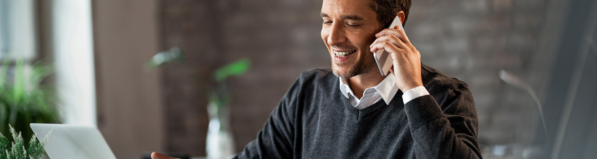 man talking on the phone at a desk smiling