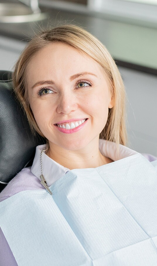 woman with blonde hair sitting in dental chair smiling