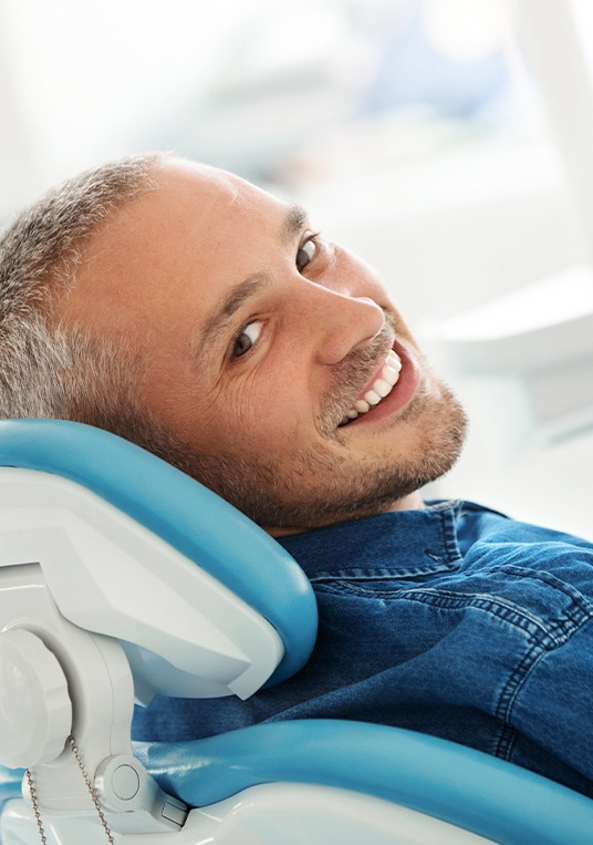 man with denim shirt sitting in a dental chair