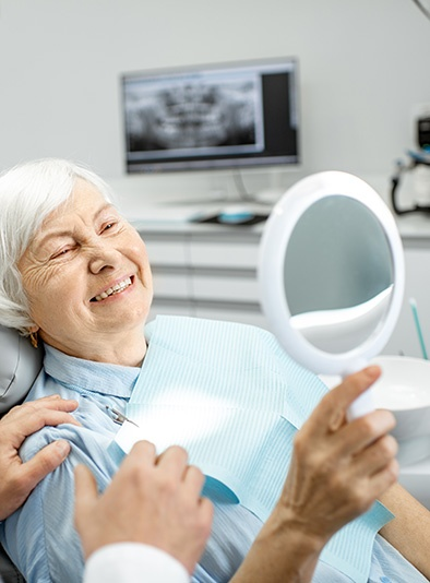 woman holding up a mirror looking at her teeth