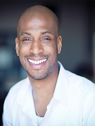 bald man in white shirt smiling