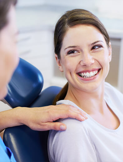 brunette woman sitting in a dental chair smiling