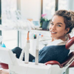 Brunette woman in a dental chair smiles after getting a dental filling in Katy, TX
