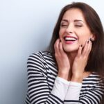 Brunette woman in a striped shirt smiles after receiving professional teeth whitening in Katy, TX