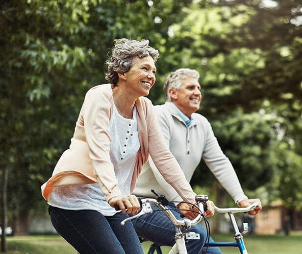 happy senior couple riding bikes together