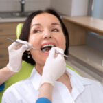 Brunette woman sits in the dentist chair while her hygienist looks at her dental sealants